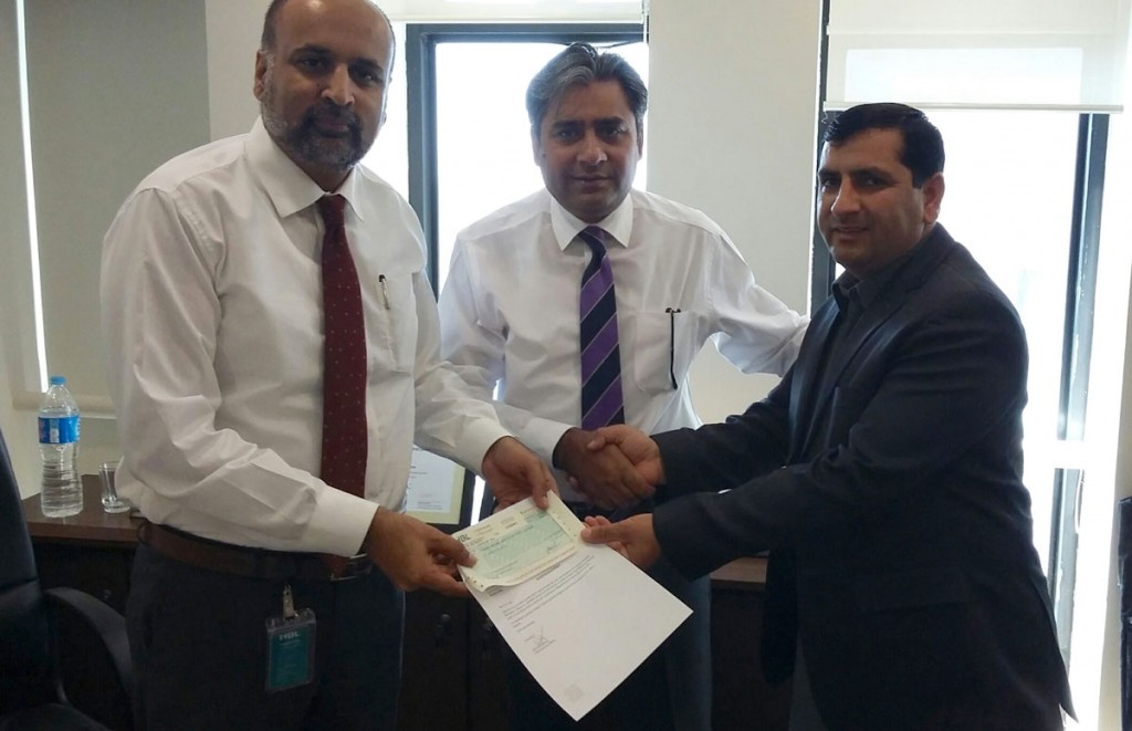 HBL Foundation officers (left) present check to Javed Iqbal (right), Executive Director, Friends Welfare Association.