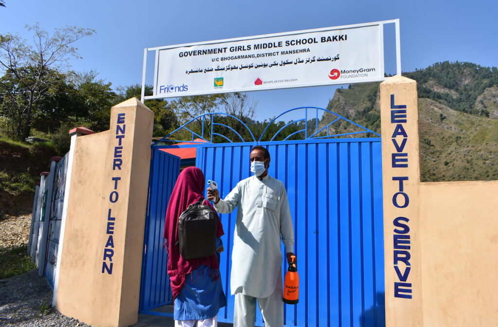 A student's temperature is taken before entering the school grounds.